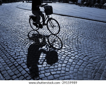 A warm spring afternoon a young girl is biking through the old streets of Copenhagen, Denmark. - stock photo