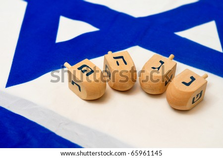A white and blue Israeli Flag with the star of David on it with wooden dreidels for the Jewish holiday of Hanukkah. - stock photo