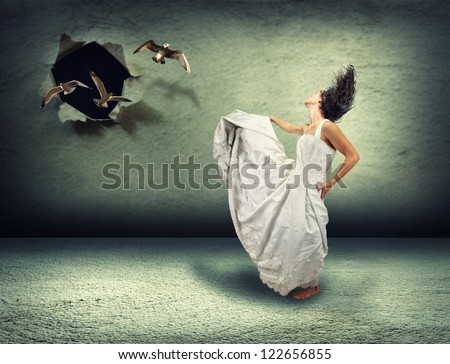 a woman dancing in an empty room made of concrete with a hole in the wall where birds are flying out - stock photo