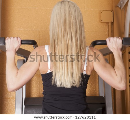 A woman doing a pull up from the back view in a gym.