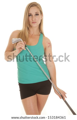 A woman holding a golf club with a serious expression. - stock photo
