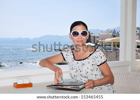 A woman holds a menu in the seaside cafe - stock photo