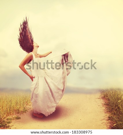 a woman in a wedding gown on a path done with a soft vintage instagram like filter - stock photo