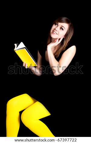 a woman in front of a black background wearing yellow tights daydreaming about the yellow book she is reading.