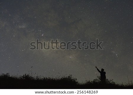 A woman looks into space and the Milky way. Long exposure photograph - stock photo