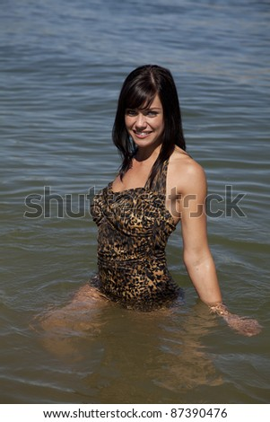 A woman standing in the water in joying the coolness of the water. - stock photo