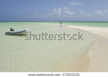 A woman walking along tropical beach with white sand and turquoise water, Caribbean Sea - stock photo