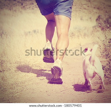 a woman with an athletic pair of legs going for a jog on grass during sunrise or sunset - healthy lifestyle concept done with an instagram like filter - stock photo