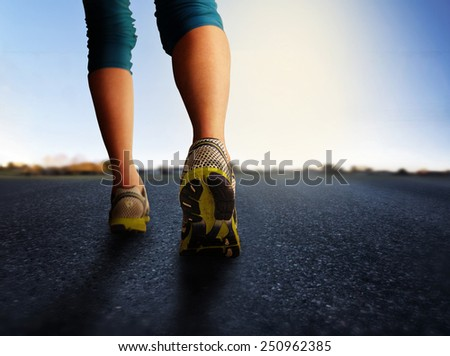 a woman with an athletic pair of legs going for a jog or run during sunrise or sunset - healthy lifestyle concept done with an instagram like filter  - stock photo