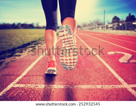 a woman with an athletic pair of legs going for a jog or run during sunrise or sunset - healthy lifestyle concept done with a retro vintage instagram like filter  - stock photo