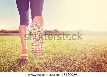 a woman with an athletic pair of legs going for a jog or run on grass during sunrise or sunset - healthy lifestyle concept done with an instagram like filter - stock photo