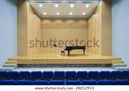 a wooden theatre on stage piano, blue seats