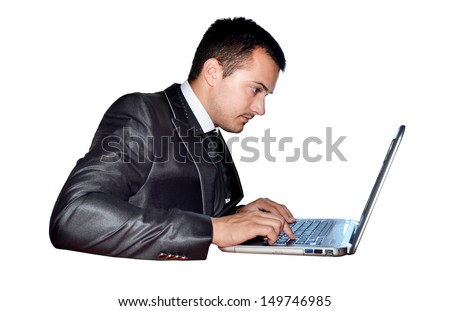 A young businessman sitting in front of a laptop isolated