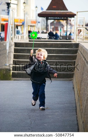 A young child unning along Burnham Promenade. - stock photo