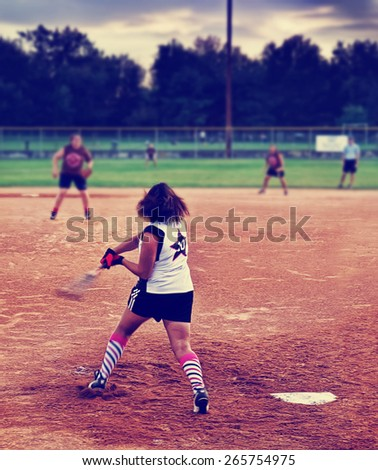 a young girl batting a ball at home plate in a softball game toned with a retro vintage instagram filter  - stock photo