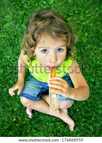 a young girl eating a frozen treat in the grass  - stock photo
