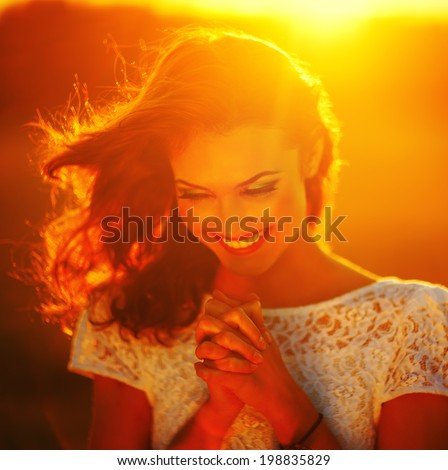 A young girl prays at sunset rays  - stock photo