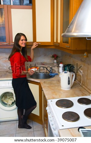 A young girl washes the dishes in the kitchen - stock photo