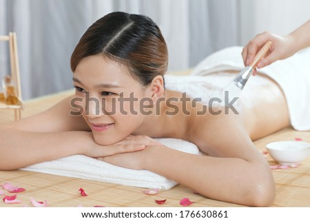 A young lady enjoy body mask in spa salon