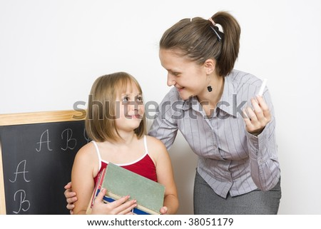 A young teacher and a little child posing, the child holding in her hand worn books, a blacboard next to them, with letters written by the pupil. - stock photo