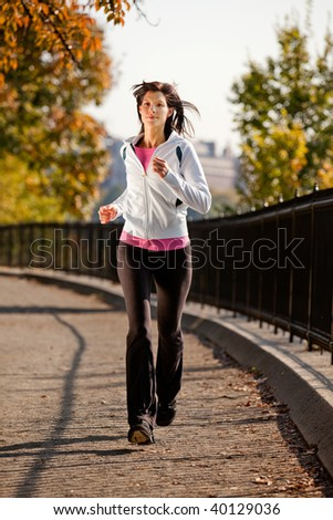 A young woman jogging in the park on a path - stock photo