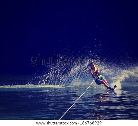 a young woman water skiing on a lake done with a retro vintage instagram filter  - stock photo