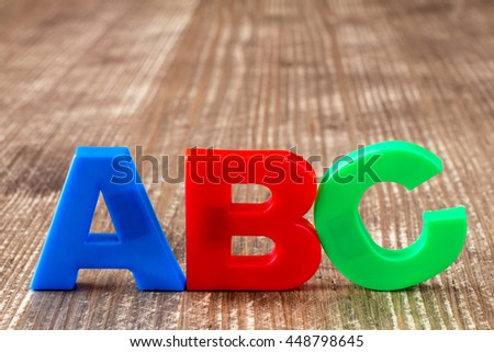 ABC spelling  of colorful plastic letters on wooden background - stock photo