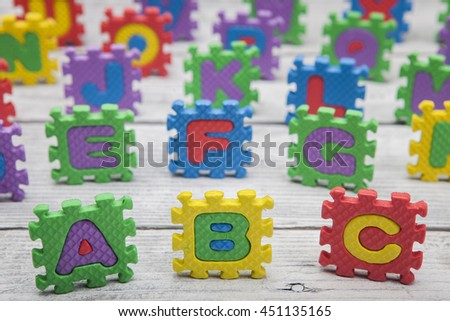"""ABC"" written with alphabet puzzle. On wooden surface - stock photo"
