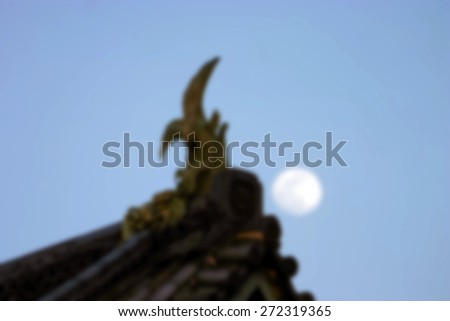 """Abstract Background Blurred Image"" Ornate roofing on a traditional Japanese building with the moon behind it.  (Blur style image) - stock photo"