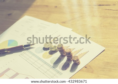 accounting,financial,Saving money concept,graph, stacks of coins ,chart and pen ,copy space,vintage,selective focus - stock photo