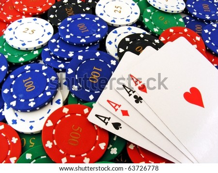4 aces lying on a pile of poker chips - stock photo