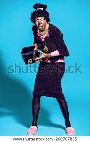 Actor dressed as an elderly old African bag in his hands on  blue background. - stock photo