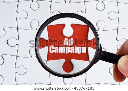 """Ad campaign"" text on red missing jigsaw puzzle with man right hand hold black magnifying glass searching for missing puzzle peace - business and finance concept - stock photo"