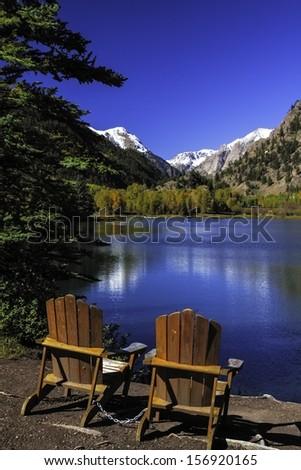 2 Adirondack Chairs sitting by blue mountain lake - stock photo