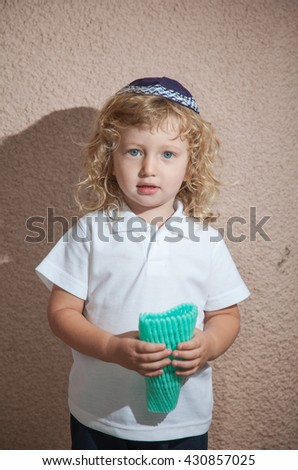 Adorable little boy with long blond curls and blue eyes in the Jewish knitted skullcap. He holds the case for the holiday citrus. Autumn holiday of Sukkot - stock photo