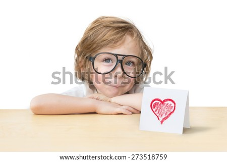 Adorable little boy with toy glasses and a red heart card on the wood table edge isolated on white background