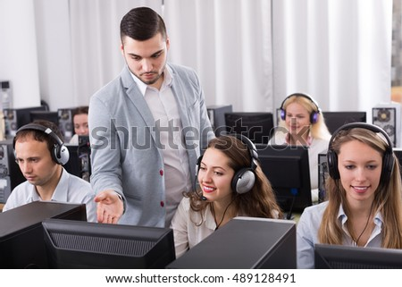 Adult boss and his successful call center team at office