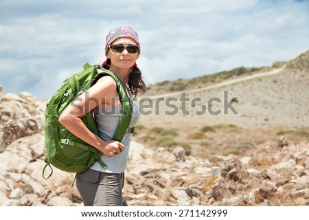 Adult brunette woman hiking and backpacking in beautiful desert and rocky landscape of south Crete, Greece. - stock photo
