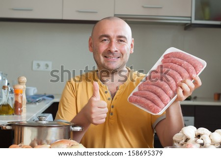 adult male  preparing meat in the kitchen - stock photo
