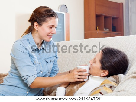 Adult woman caring for sick mature mother in living room at home - stock photo