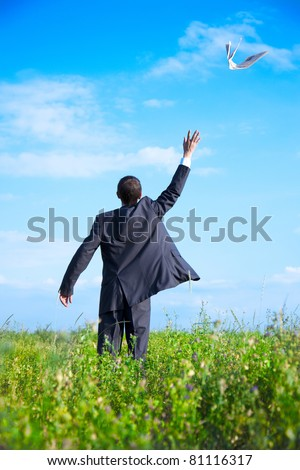 Adult young businessman in the newspaper scattered in the sky. flown apart in the sky newspaper - stock photo