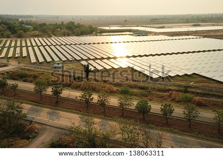 Aerial photo of solar power plant  reflected sunlight from sunset. - stock photo