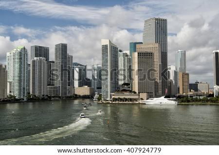 Aerial view of Miami skyscrapers with cloudy sky, boat sailing next to Miami downtown - stock photo