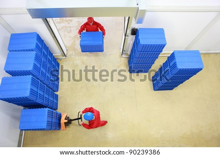 Aerial view of two workers working with  plastic blue boxes in small warehouse - stock photo