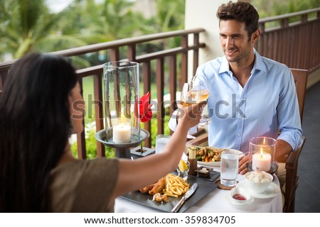 Affectionate couple having dinner on the balcony tropical resort - stock photo