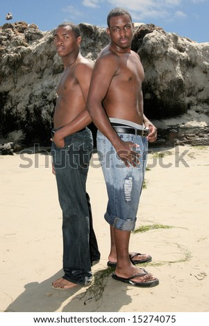 2 African American Siblings Standing on the Beach - stock photo