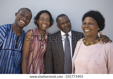 4 African people standing together against a wall with happy expressions. Thye look like family. - stock photo