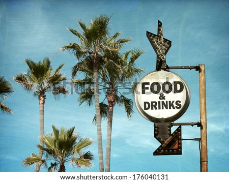 aged and worn vintage food and drinks sign on beach with palm trees                              - stock photo