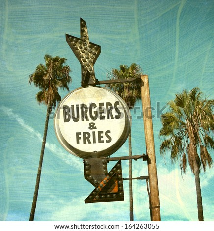 aged and worn vintage photo of burger and fries sign                             - stock photo