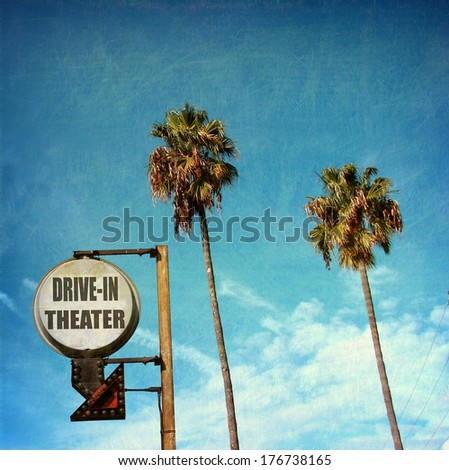 aged and worn vintage photo of  drive in theater sign with palm trees                             - stock photo